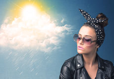 Young person looking with sunglasses at clouds and sun. Concept on blue background Royalty Free Stock Image