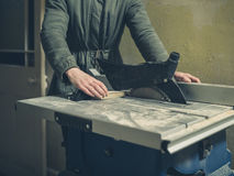 Young person operating tablesaw Stock Image