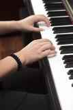 Young person playing the piano with both hands Stock Photo