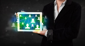 Young person presenting tablet with green social media icons Stock Image