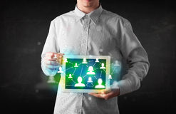 Young person presenting tablet with green social media icons Royalty Free Stock Photography