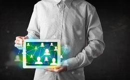 Young person presenting tablet with green social media icons Stock Images