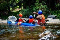 Young person are rafting in river with guide tour adjutant. Candid shot real time in light nature royalty free stock images