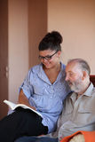 Young person reading to elderly man Royalty Free Stock Image