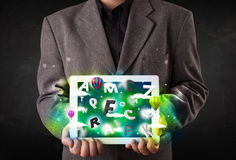 Young person showing tablet with abstract letters and sky Royalty Free Stock Images