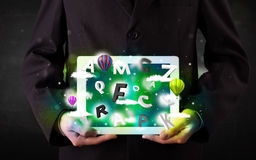 Young person showing tablet with abstract letters and sky Royalty Free Stock Photo