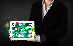 Young person showing tablet with abstract letters and sky Royalty Free Stock Photography