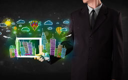 Young person showing tablet with hand drawn cityscape Royalty Free Stock Images