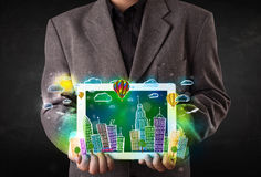 Young person showing tablet with hand drawn cityscape Stock Images