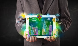 Young person showing tablet with hand drawn cityscape Stock Photos