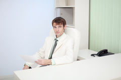 Young person sits at office on workplace Royalty Free Stock Photography