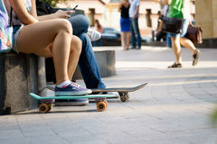 Young person sitting with skateboards and resting on summer day. Movement, sport, healthy lifestyle concept Royalty Free Stock Photo