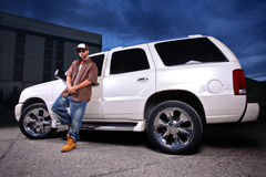 Young person standing next to SUV. Young person standing next to big SUV Royalty Free Stock Photo
