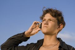 Young person with telephone. Boy with telephone on sky background Stock Image