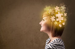 Young person thinking with glowing puzzle mind Stock Photos