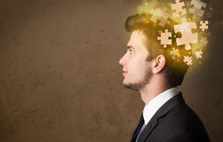 Young person thinking with glowing puzzle mind. On grungy background Stock Photo
