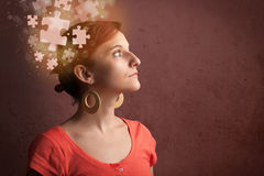 Young person thinking with glowing puzzle mind Stock Photo