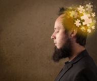 Young person thinking with glowing puzzle mind. On grungy background Stock Photos