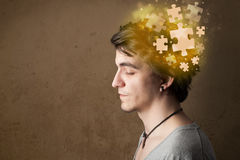 Young person thinking with glowing puzzle mind. On grungy background Stock Photography