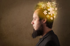 Young person thinking with glowing puzzle mind. On grungy background Stock Images