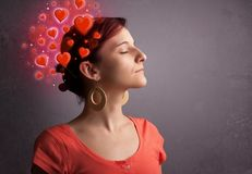 Young person thinking about love with red hearts. Young person thinking about love with glowing red hearts stock photography