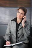 Young personal assistant using mobile smiling. Young attractive personal assistant setting appointment on phone, smiling stock photos