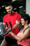 Brunette woman working out with personal coach. Young personal coach working with middle aged female client in gym. Brunette women exercising on machine. Healthy royalty free stock photo