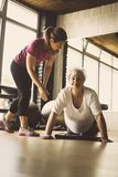 Young personal trainer helping senior. Woman. Workout in rehabilitation center Stock Photography