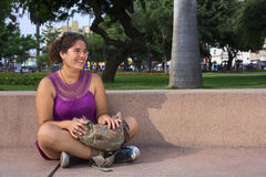 Young Peruvian Woman Cross-Legged. Beautiful smiling young Peruvian woman sitting cross-legged in a park in Lima, Peru (Selective Focus, Focus on the face of the Stock Photo