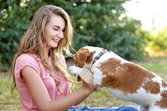 Cute girl is playing with her dog in the park. Young pet dog breeds beagle walking in park outdoors. woman carefully walks puppy, plays and trains, sits with pet stock photos