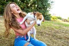 Cute girl is playing with her dog in the park. Young pet dog breeds beagle walking in park outdoors. woman carefully walks puppy, plays and trains, sits with pet royalty free stock image