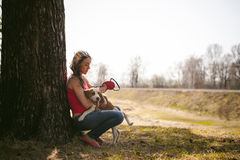 Young pet dog breeds beagle walking in the park outdoors. Young pet dog breeds beagle walking in park outdoors. woman carefully walks puppy, plays and Stock Image