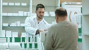 Young pharmacist giving drug to senior man customer and taking payment in dollars at drugstore. Young pharmacist giving drug to senior men customer and taking royalty free stock image