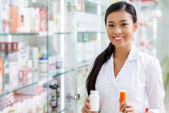 Young pharmacist holding containers with medication and smiling at camera. In drugstore stock photos