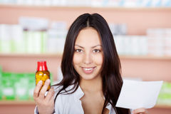 Young pharmacist holding medicine and prescription Royalty Free Stock Image