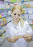 Young Pharmacist looking at a prescription Royalty Free Stock Photo