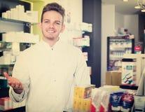 Young pharmacist standing among shelves Royalty Free Stock Image