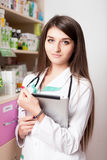 Young pharmacist woman with digital tablet in hands Stock Photo