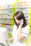 Young pharmacist woman expressing wonder while having a phone call. Pharmaceutical background. Drugstore. Pills and medicine. Royalty Free Stock Image