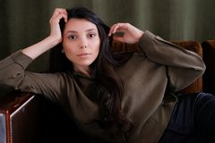 A young photogenic portfolio girl or model is lying on the couch looking at the camera with a calm look. The concept of fashion royalty free stock photo