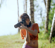Young photographer. Young girl with SLR camera take a picture Royalty Free Stock Photos