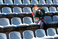 Young Photographer. Sitting in the stands and photograph game Stock Photography