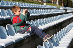 Young Photographer. Sitting in the stands and photograph game Stock Image
