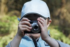 Young photographer. Young boy 6 years old takes a photograph with his compact camera Royalty Free Stock Photo