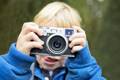 Young Photographer. Holding a retro rangefinder camera in front of his face, taking a picture Royalty Free Stock Photography