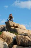 Young Photographer. Photographer seated on a Big Rock against blue Sky Royalty Free Stock Photos