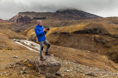 Young photographer on the background of volcanic rocks. Royalty Free Stock Photography