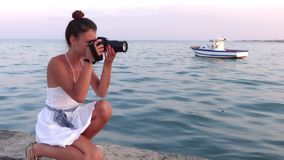 Young photographer. Blue sea and little boat on background. stock video footage