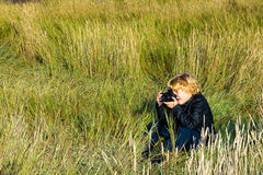 Young Photographer. Sitting in the long grass taking photographs Stock Photos