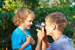 Young photographer with camera shoots her brother Stock Photo